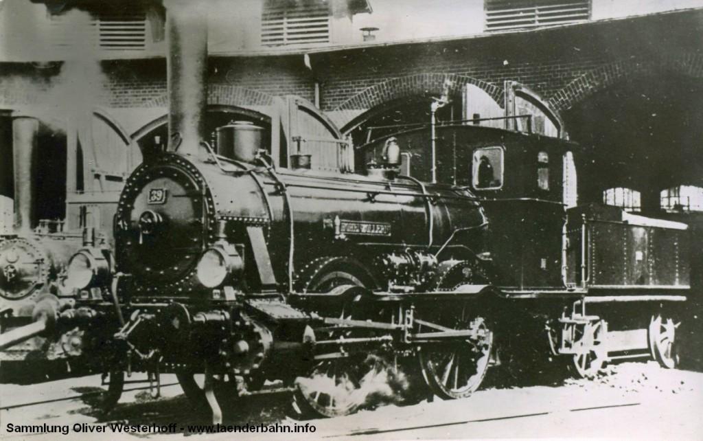 """Die Nummer 39 """"HOHENZOLLERN"""" wurde 1876 von der gleichnamigen Maschinenfabrik an die G.O.E. ausgeliefert. Vorgesehen für die Nummer 51 7013 wurde die Lok jedoch bereits zwischen 1923 und 1925 ausgemustert. Das Bild zeigt sie im Betriebswerk, vermutlich in Oldenburg. Im Hintergrund ist noch eine T 1.2 zu erkennen."""