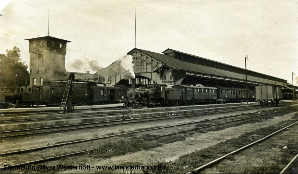 """Bilder von der Gleisseite sind äußerst selten, dieses um 1913 entstandene zeigt vor der Bahnsteighalle die oldenburgische P 4.1 Nr. 140 """"RABE"""" und eine unbekannte T Bilder von der Gleisseite sind äußerst selten, dieses um 1913 entstandene zeigt vor der Bahnsteighalle die oldenburgische P 4.1 Nr. 140 """"RABE"""" und eine unbekannte T2.2."""