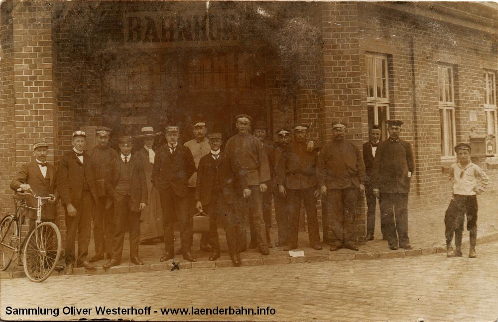 """Bereits 1912 angefertigt wurde das folgende Bild. Vor dem Eingang zum Bahnhof haben dich Gepäckträger versammelt, dazu ein """"uniformierter"""" G.O.E.-Beamter und einige Angestellte von Hotels."""