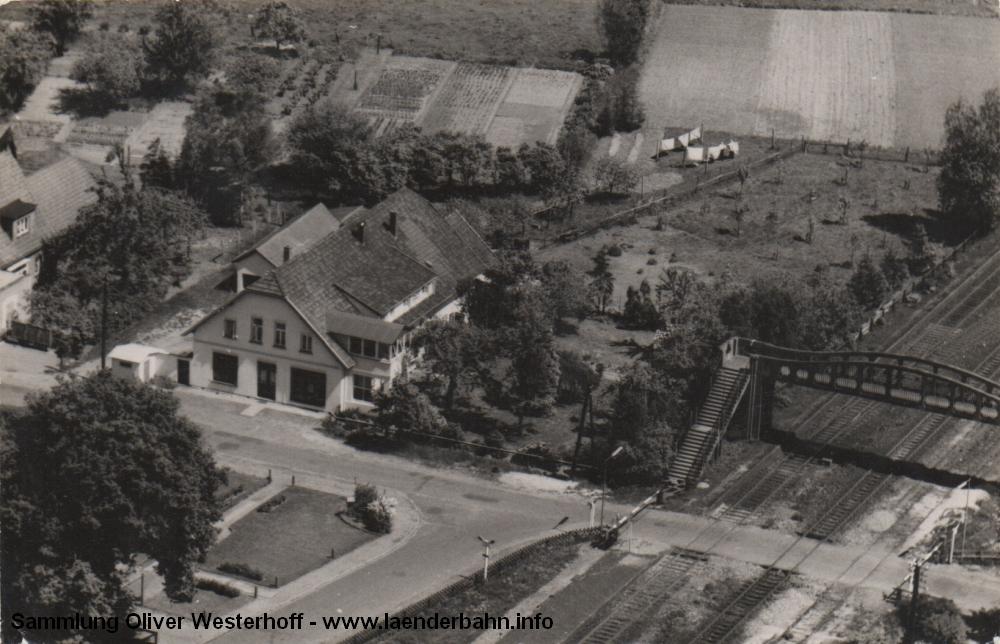 Das Luftbild von Anfang der 1960er Jahre zeigt noch einmal den Bahnübergang mit der Fussgängerbrücke.