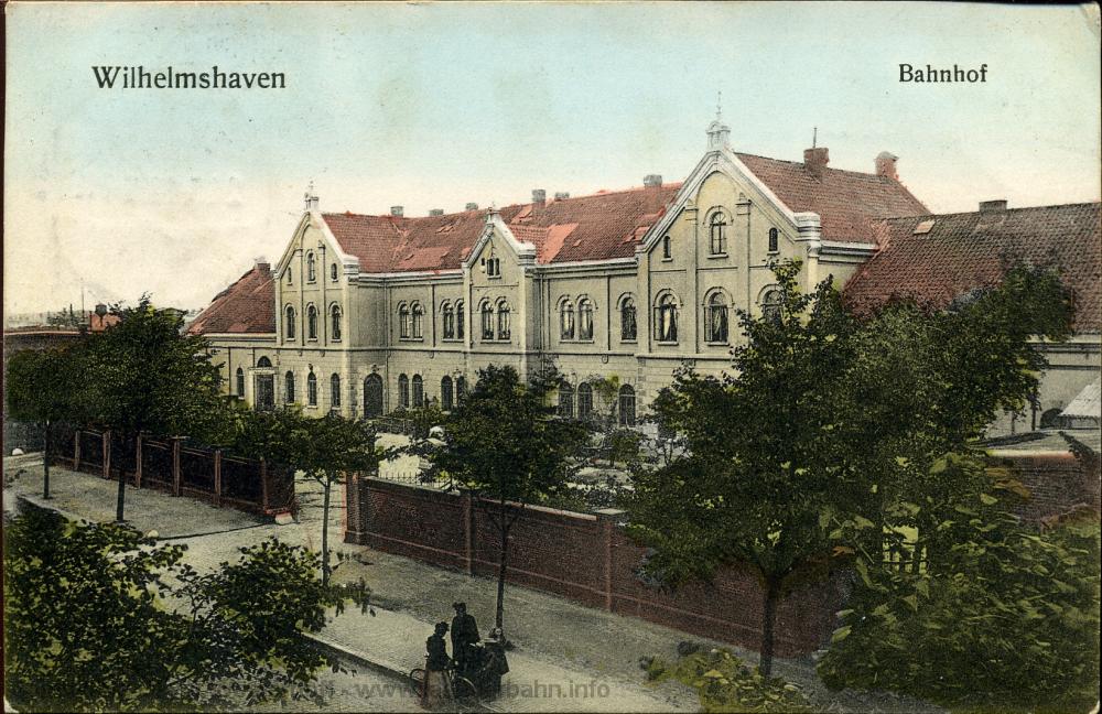 Die Straßenseite des Bahnhofs Wilhelmshaven um 1910. Noch ist der Vorplatz durch eine Mauer und Tore zur Straße hin abgeschlossen.