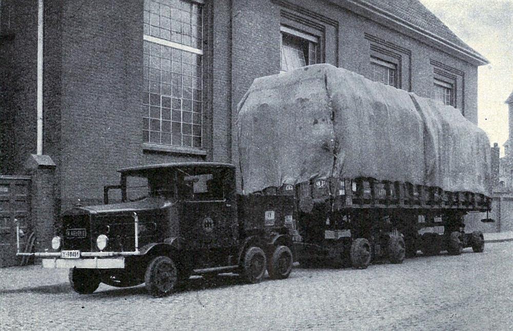 Hochbeladener Rungenwagen auf einem Straßenfahrzeug vor dem Werk der Firma Kaiser