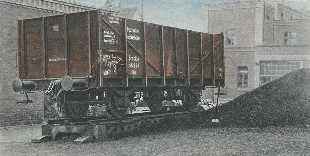 Ein offener Güterwagen auf einer mobilen Absetzvorrichtung steht zum Be- oder Entladen bereit